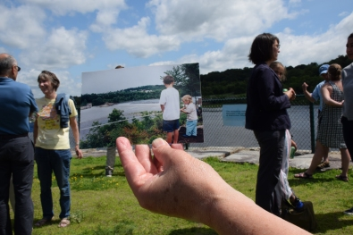 man holds up snapshot of river 20 years ago showing himself as child at same spot