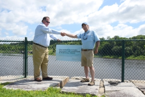 """Greg and ? shake hands in front of Steve Brooke's quote on banner. """"The restoration includes the Kennebec's full compliment of diadromous fishery"""""""